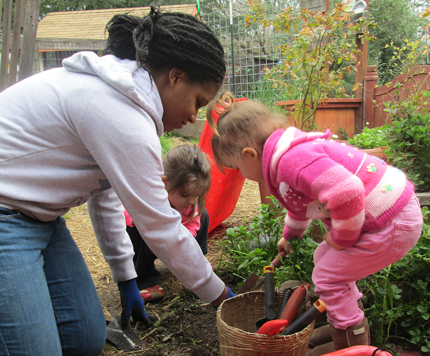 Children and adult planting in the garden
